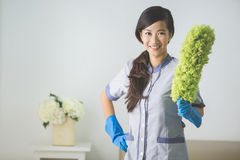 Cleaner maid woman with duster. And uniform cleaning living room at home Stock Photo