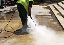 Cleaner of the pavement of the street with pressurized water. Municipal cleaning worker clean the dirt from sidewalk pavement with a pressurized water machine Royalty Free Stock Image