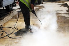 Cleaner of the pavement of the street with pressurized water. Municipal cleaning worker clean the dirt from sidewalk pavement with a pressurized water machine Royalty Free Stock Photography