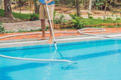 Cleaner of the swimming pool . Man in a blue shirt with cleaning equipment for swimming pools, sunny Stock Images
