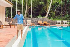 Cleaner of the swimming pool . Man in a blue shirt with cleaning equipment for swimming pools, sunny Royalty Free Stock Photos