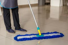 Cleaner washes a MOP tiled floors, cleaning royalty free stock photo