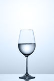 Cleaner water in the fixed wineglass while standing on the clean glass against light background. Royalty Free Stock Photos
