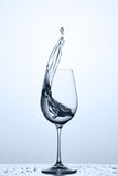 Cleaner water splash out of wineglass while standing on the glass with droplets against light background. Royalty Free Stock Photo