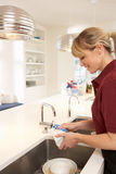 Cleaner Working In Domestic Kitchen Stock Photography