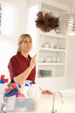 Cleaner Working In Domestic Kitchen. With Feather Duster Royalty Free Stock Images