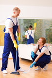 Cleaners with a broom. Professional cleaners with a broom during work in living room royalty free stock photography
