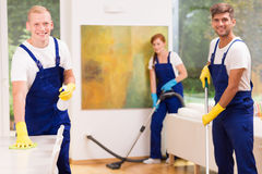 Cleaners cleaning modern apartment. Group of professional cleaners cleaning modern apartment royalty free stock photos