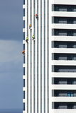 Cleaners hanging on tower building Stock Photo