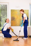 Cleaners with vacuum cleaner. Professional cleaners with vacuum cleaner in living room Royalty Free Stock Photography