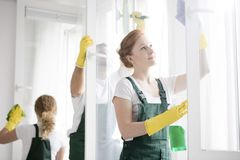 Cleaners washing windows. Team of the three cleaners in yellow gloves and green overalls washing windows stock photo
