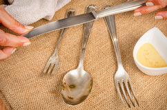 Cleanign silverware. Female hands cleaning spotty silverware with a cleaning product and a cloth Stock Image