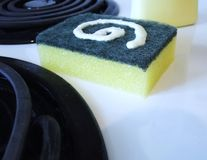 Cleaning. Yellow and green Sponge with household cleaning product on a white stove Royalty Free Stock Photography