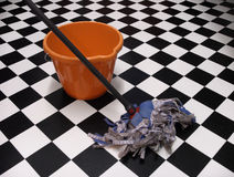 Cleaning. A mop and bucket on a chequered floor stock photo