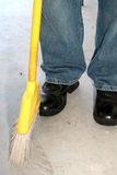 Cleaning. Man showing jeans and boots and bottom of yellow broom Royalty Free Stock Images