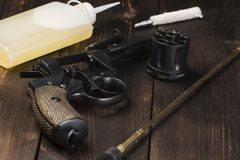 Cleaning an antique revolver on a table. Cleaning an antique revolver on a wooden table. with complete disassembly. Oil, brush, ramrod royalty free stock photo