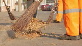 Cleaning autumn leaves on the street. Street cleaner sweeping autumn park, low-paid job, no prospects in life stock video footage