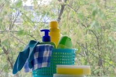 Cleaning. Basket with sponges and bottles of chemicals. Rubber gloves and paper towel. Household chemicals stock images