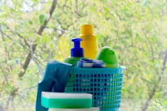 Cleaning. Basket with sponges and bottles of chemicals. Rubber gloves and paper towel. Household chemicals stock photos
