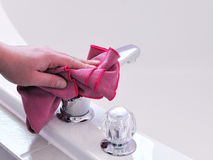 Cleaning the bath tub and tap. Man's hand with microfibre cloth polishing a tap Royalty Free Stock Images