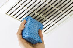 Cleaning Bathroom Fan Vent Cover with Sponge Royalty Free Stock Image