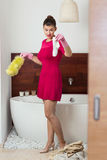 Cleaning bathroom in rose dress Stock Images