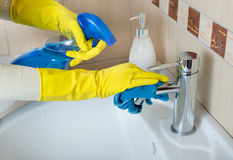 Cleaning bathroom sink and faucet Royalty Free Stock Image