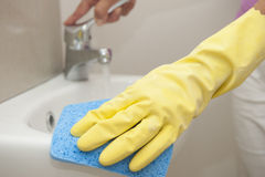 Cleaning bathroom sink in rubber glove Stock Image