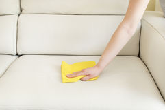 Cleaning a beige sofa with a yellow cloth. Young woman cleaning a beige sofa with a yellow cloth Royalty Free Stock Image