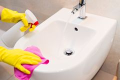 Cleaning bidet in wc with pink cloth. Hands with yellow rubber gloves cleaning bidet in wc with pink cloth. Spring cleaning Royalty Free Stock Images