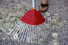 Cleaning black dolar money with rake, metaphor stock images
