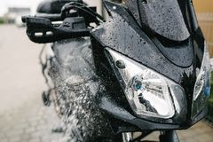 Cleaning black touristic motorbike Royalty Free Stock Photos