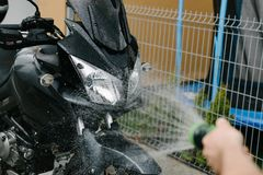 Cleaning black touristic motorbike Stock Images