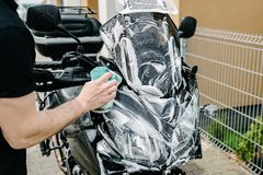 Cleaning black touristic motorbike with water Royalty Free Stock Photo