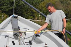 Cleaning The Boat. Middle aged man cleaning his dingy boat in his back yard after a day's sailing Stock Image