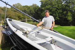 Cleaning The Boat. Middle aged man cleaning his dingy boat in his back yard after a day's sailing Stock Photography