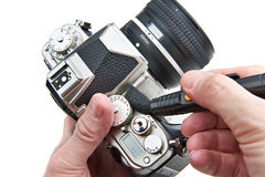 Cleaning body photographic DSLR camera with brush isolated Royalty Free Stock Photos