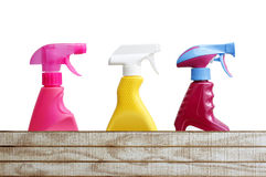 Cleaning bottles. Three cleaning bottles above wood Stock Image