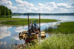 Clean up the lake. Cleaning the bottom of the lake with a dredge stock photos