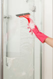 Cleaning a shower with a squeegee Royalty Free Stock Photo