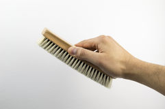 Cleaning brush. Hand holding a cleaning brush on white background Royalty Free Stock Photo