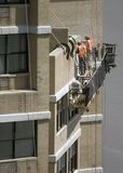 Cleaning a building. Workers on a lift on the side of a building performing maintenance work royalty free stock image