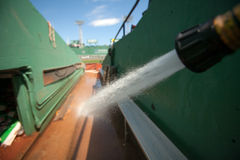 Cleaning Canvas Alley. A water hose is being used to spray down Canvas Alley, the open alley behind the first base line at Fenway Park, where the grounds crew Royalty Free Stock Photography