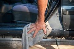 Car washing. Man washing and cleaning his car at home Stock Image