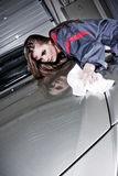 Cleaning Car. A beautiful woman in a car mechanic uniform cleaning a silver colored car, in a workshop Stock Photo