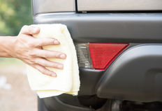 Cleaning car with microfiber cloth polishing car The back of car. Hand cleaning car with microfiber cloth polishing car The back of car Stock Photos