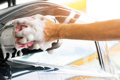 Cleaning a car with sponge. Auto service staff cleaning a car with sponge and car wash-car detailing and valet concepts Royalty Free Stock Images