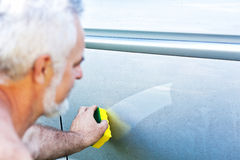 Cleaning car using a cleaning sponge Stock Photo