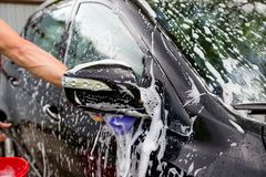 Cleaning automobile Using High Pressure Water. Man washing his car under high pressure water in service.worker washing stock image