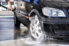 Man washing his car under high pressure water in service Stock Photos